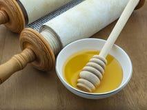 Weiße Untertasse mit goldenem Honig auf dem Hintergrund von Torah-Rollesymbolen des jüdischen neuen Jahres Lizenzfreie Stockfotografie