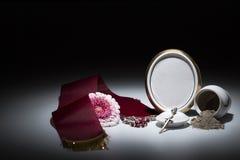 Weiße Urne mit leerem Trauerrahmen, Blume, Band und Rosenbeet für Stockbilder
