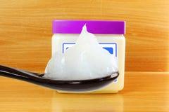 Weiße Vaseline im Löffel mit Glas lizenzfreies stockfoto