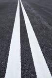 Weiße Verkehrslinien Markierung auf Asphaltstraße Stockfoto