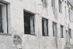 Weiße Wand eines verlassenen Gebäudes Unterbrochenes Windows Stockbild