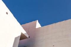 Weiße Wand im Gegensatz zu einem blauen Himmel Lizenzfreie Stockfotos