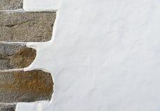 Weiße Wand mit einer Steinecke Stockbild