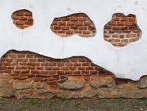 Weiße Wand mit mit orange Ziegelsteinen und Steinen Lizenzfreies Stockbild