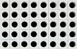 Weiße Wand mit schwarzen Löchern Stockbild