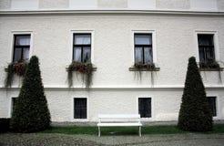 Weiße Wand mit vier langen Fenstern und Anlagen, zwei Konus-förmige Büsche und eine weiße Bank stockfotografie
