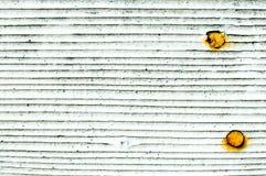 Weiße Wandschindeln der Hintergrundbeschaffenheit mit verrosteten Nägeln lizenzfreie stockbilder