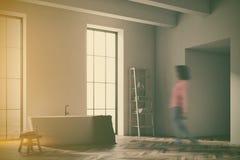Weiße Wanne in einer grauen Badezimmereckenunschärfe Stockbilder