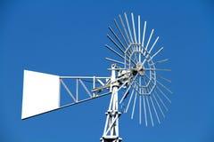 Weiße Wasserpumpenwindmühle auf Hintergrund des blauen Himmels Stockfoto