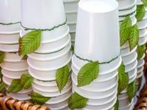Weiße Wegwerfschalen Stapel der Weißbuchschalendekoration mit grünen Blättern lizenzfreie stockbilder