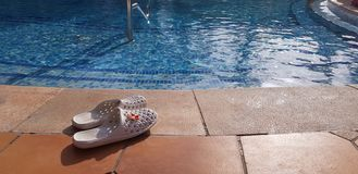 Weiße weibliche Flipflops verließen nahe Swimmingpool lizenzfreie stockfotografie