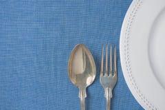Weiße Weinlese-leerer Platten-Halbkreis-Silber-Gabel-Löffel auf hellblauem Leinengewebe Unbedeutendes japanische Art-Gedeck Stockfotografie