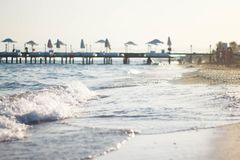 Weiße Welle auf dem sandigen Strand Das Ufer des blauen Meeres gegen den Pier Pier durch das Meer in der Türkei lizenzfreie stockbilder