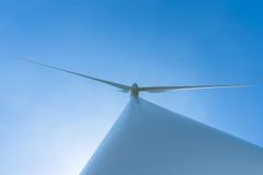 Weiße Windkraftanlage, die Strom auf blauem Himmel erzeugt Lizenzfreies Stockfoto