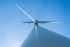 Weiße Windkraftanlage, die Strom auf blauem Himmel erzeugt Stockbild