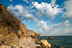 weiße Wolken über dem felsigen Strand, dem Meer und der Luft Stockbilder