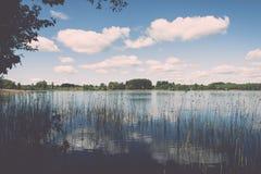Weiße Wolken auf dem blauen Himmel über blauem See - Retro- Weinlese effe Stockfoto
