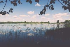 Weiße Wolken auf dem blauen Himmel über blauem See - Retro- Weinlese effe Stockbilder