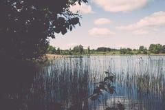 Weiße Wolken auf dem blauen Himmel über blauem See - Retro- Weinlese effe Lizenzfreie Stockfotos