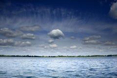 Weiße Wolken auf dem blauen Himmel über dem See Lizenzfreie Stockfotos