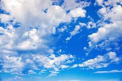Weiße Wolken auf einem blauen Himmel Empfindliche flaumige weiße Wolken im Sonnenlicht gegen einen blauen Himmel Nahtloser Sommer Stockbild