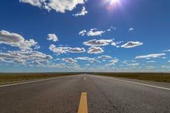 Weiße Wolken des blauen Himmels der Wiesenlandstraße stockbilder