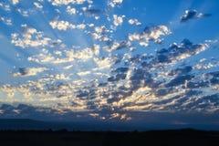Weiße Wolken im blauen Himmel über den Bergen, Dämmerung Das Sonne ` s stockbild