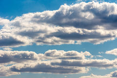 Weiße Wolken schwimmen langsam über den blauen Himmel Lizenzfreie Stockfotos