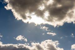 Weiße Wolken schwimmen langsam über den blauen Himmel Stockfotografie