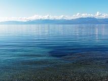 Weiße Wolken und blaue Berge reflektiert im Ozean Lizenzfreies Stockfoto