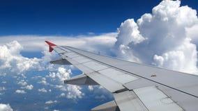Weiße Wolken und blauer Himmel als gesehenes durch Fenster eines Flugzeuges Reise- und Ferienkonzept stockfotografie
