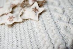 Weiße woolen gestrickte Strickjacke mit Sterndekorationen Stockbilder