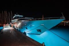 Weiße Yacht mit einer leuchtenden Unterseite ist im Jachthafen nachts Lizenzfreie Stockfotos