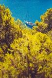 Weiße Yacht nehmen einen Schutz in der schönen blauen Lagune von Assos-Dorf Kefalonia Feld zwischen Spitze der grünen Kiefer lizenzfreies stockfoto