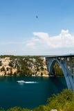 Weiße Yacht unter maslenica Brücke mit den Banken bedeckt mit grünem Kiefernwald- und -schwalbenfliegen im bewölkten Himmel Lizenzfreies Stockbild