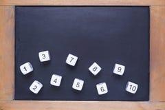 Weiße Zahl würfelt auf kleiner hölzerner gestalteter Tafel Lizenzfreie Stockfotografie