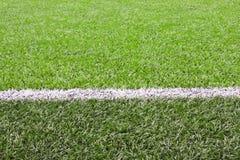 Weiße Zeile auf einem Fußballplatzgras stockbild