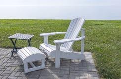 Weißer Adirondack-Stuhl durch den See Lizenzfreie Stockfotos