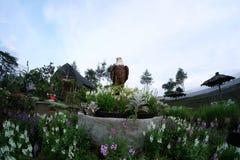 Weißer Adlerkopf der Statue mit dem braunen Pelz umgeben durch sortierte Blumen im schönen Garten Stockfoto