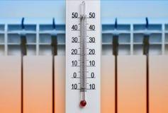 Weißer Alkoholraumthermometer zeigt eine bequeme Temperatur im Haus vor dem hintergrund eines Heizungsheizkörpers lizenzfreie stockbilder