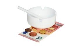 Weißer Aschenbecher mit Zigarette, Eurobanknoten und Münzen lizenzfreie stockbilder