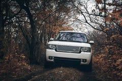 Weißer Auto Land-Rover Range Rover-Stand auf der Landschaft nicht für den Straßenverkehr an den drastischen Wolken Tages Stockfotografie