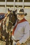 Weißer bärtiger Cowboy durch sein Pferd stockfotografie
