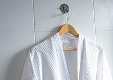 Weißer Bademantel auf Aufhänger auf Weiß Stockbild