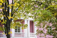 Weißer Balkon des rosa Hauses der klassischen Art im Herbstgarten Stockfotografie