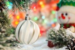 Weißer Ball hängt an einer schneebedeckten Niederlassung eines Weihnachtsbaums gegen einen fröhlichen Schneemann und bunten Licht Stockfotografie