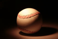 Weißer Baseball auf dunklem Hintergrund Lizenzfreies Stockbild