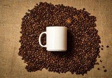Weißer Becher, der auf Stapel von Röstkaffeebohnen auf Leinenstoff liegt Stockbild