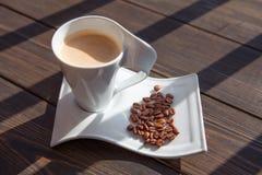 Weißer Becher Kaffee mit Körnern Stockfoto