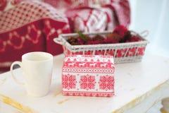 Weißer Becher mit einem Geschenk auf dem Tisch im neuen Jahr Stockfotos
